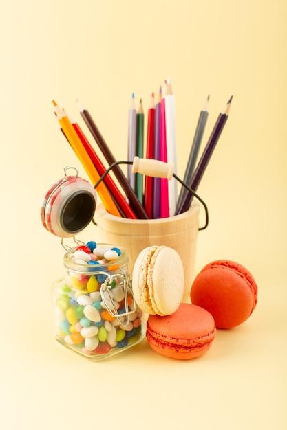 Uma vista frontal de doces coloridos com macarons franceses e lápis multicoloridos Foto gratuita