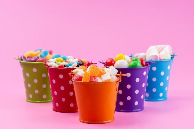 Uma vista frontal de doces diferentes, como doces confitures marmeladas dentro de cestas na cor rosa, açúcar doce Foto gratuita