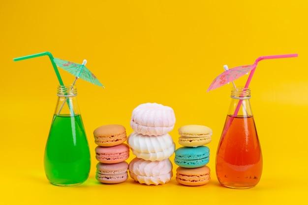 Uma vista frontal de macarons franceses junto com merengues e drinks coloridos em bolachas amarelas Foto gratuita