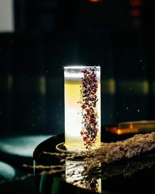 Uma vista frontal de um coquetel gelado fresco e glacê dentro de um copo longo na superfície escura e escura com bar de coquetéis de suco Foto gratuita