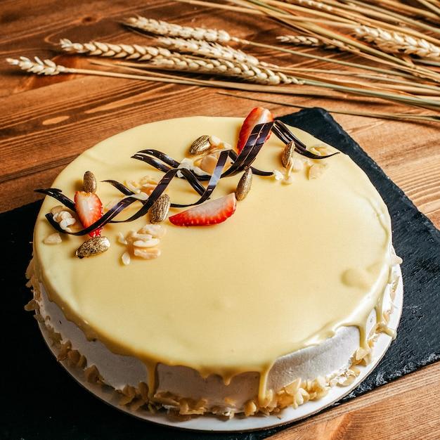 Uma vista frontal delicioso bolo de aniversário decorado gostoso redondo dentro de placa branca aniversário doce biscoito no fundo marrom Foto gratuita