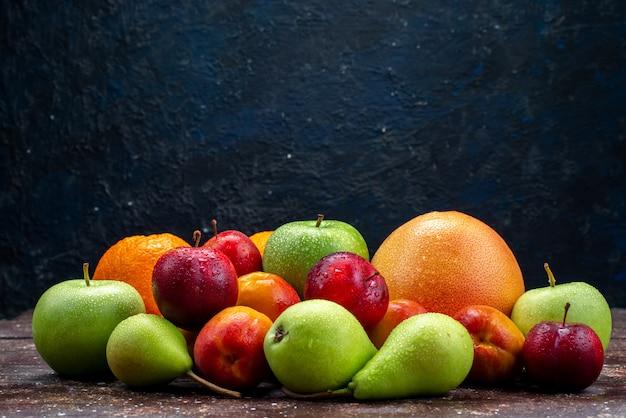 Uma vista frontal diferentes frutas maçãs frescas peras ameixas laranjas no fundo escuro composição de frutas cor do arco-íris Foto gratuita