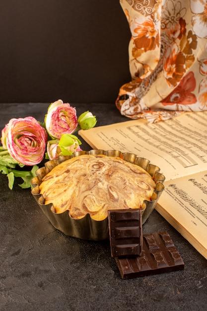 Uma vista frontal doce redondo bolo gostoso delicioso dentro de bolo pan junto com barras de choco flores e caderno de notas musicais sobre o fundo cinza biscoito de açúcar Foto gratuita