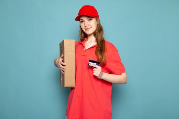 Uma vista frontal feminino atraente correio em camisa polo vermelha boné vermelho e calça jeans segurando a caixa posando sorrindo sobre o trabalho de serviço de alimentação de fundo azul Foto gratuita