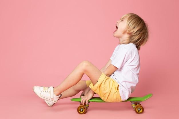 Uma vista frontal gritando menino loiro de cabelos adorável andando de skate verde no espaço rosa Foto gratuita