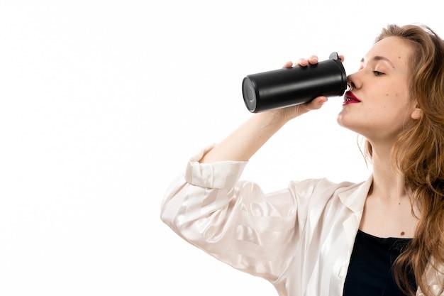 Uma vista frontal jovem atraente de camisa preta e calça preta, segurando uma garrafa térmica preta bebendo no branco Foto gratuita