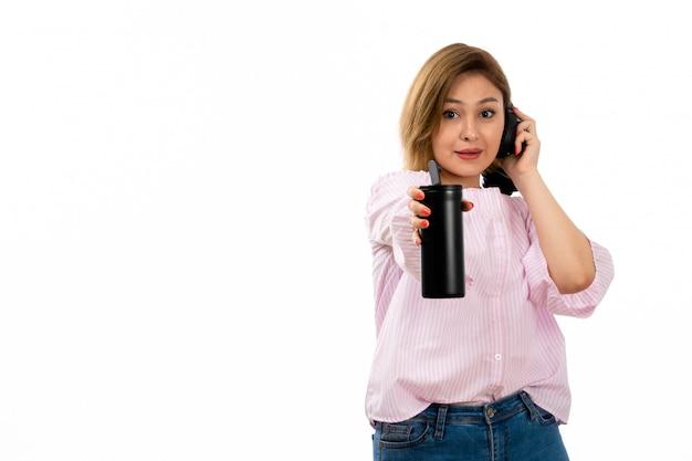 Uma vista frontal jovem atraente de camisa rosa e calça jeans azul com fones de ouvido pretos bebendo segurando a garrafa térmica preta fones de ouvido preto música em branco Foto gratuita