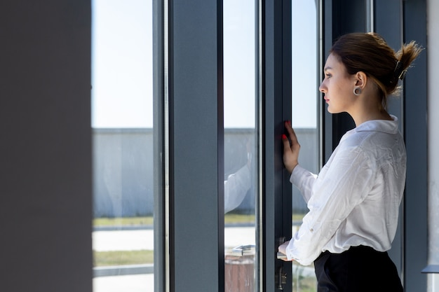 Uma vista frontal jovem bonita em calças de camisa branca e preta, olhando para a distância através da janela no corredor esperando durante o dia, construindo atividade de trabalho Foto gratuita