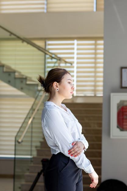 Uma vista frontal jovem bonita em calças de camisa branca e preta, olhando para a distância no corredor esperando durante o dia, construindo atividade de trabalho Foto gratuita