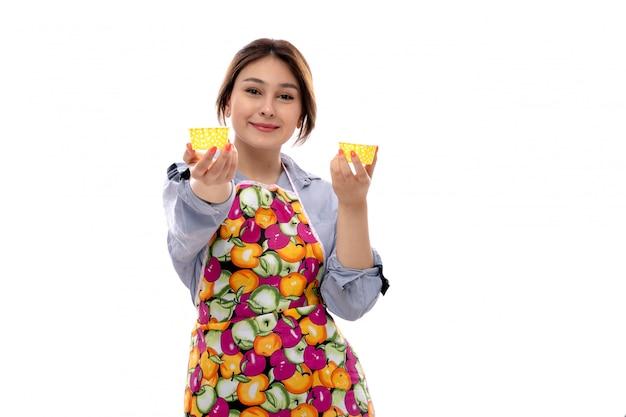 Uma vista frontal jovem bonita na camisa azul clara e capa colorida segurando panelas de bolo amarelo sorrindo feliz Foto gratuita