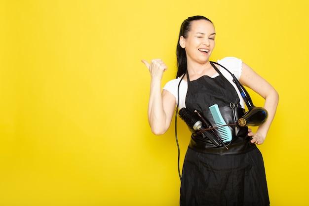 Uma vista frontal jovem cabeleireiro feminino na capa branca de camiseta preta com pincéis e secador de cabelo sorrindo posando de boas-vindas Foto gratuita