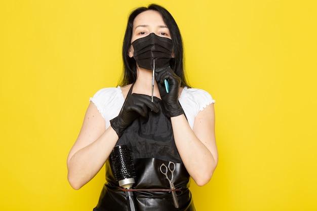 Uma vista frontal jovem cabeleireiro feminino na capa branca de camiseta preta, segurando uma tesoura em luvas estéreis pretas de máscara preta Foto gratuita