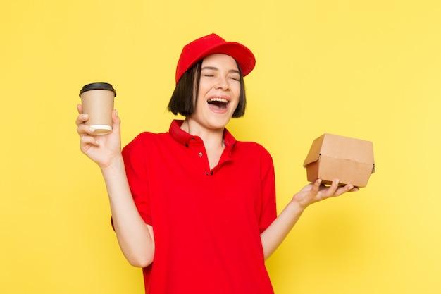 Uma vista frontal jovem correio feminino em luvas pretas uniformes vermelhas e boné vermelho segurando a caixa de alimentos e a xícara de café Foto gratuita