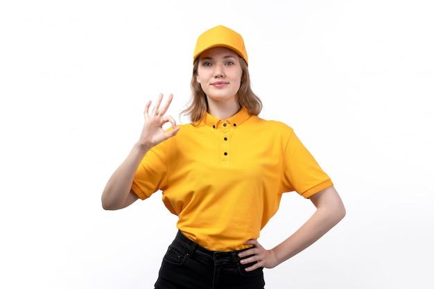 Uma vista frontal jovem correio feminino trabalhadora do serviço de entrega de comida posando com sinal bem sorrindo em branco Foto gratuita