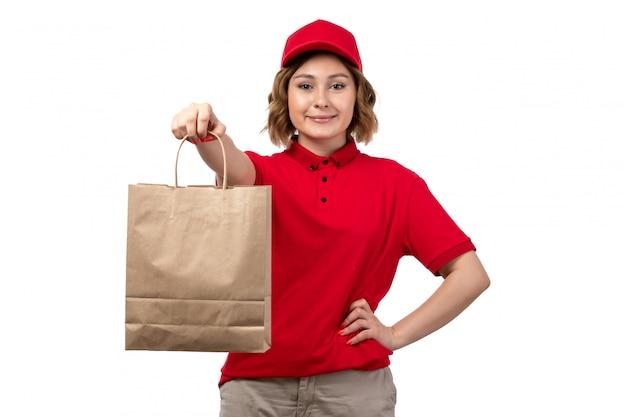 Uma vista frontal jovem correio feminino trabalhadora do serviço de entrega de comida segurando o pacote de entrega de comida sorrindo em branco Foto gratuita