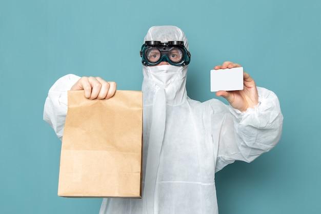 Uma vista frontal jovem do sexo masculino em um terno especial branco e segurando um cartão branco e um pacote na parede azul homem terno perigo cor de equipamento especial Foto gratuita