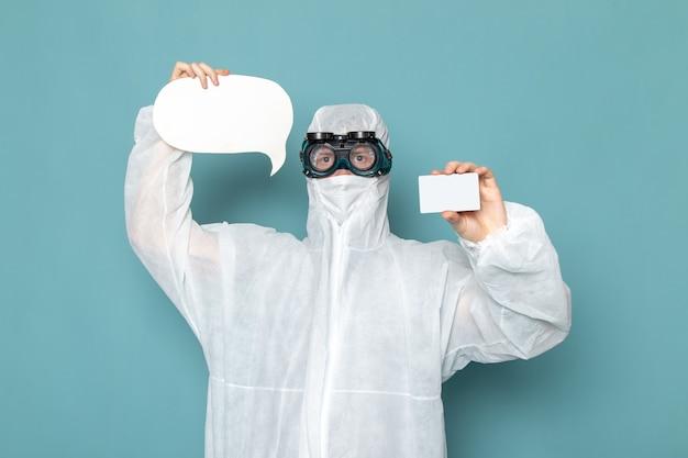 Uma vista frontal jovem do sexo masculino em um terno especial branco e segurando um cartão branco e um sinal na parede azul. Foto gratuita