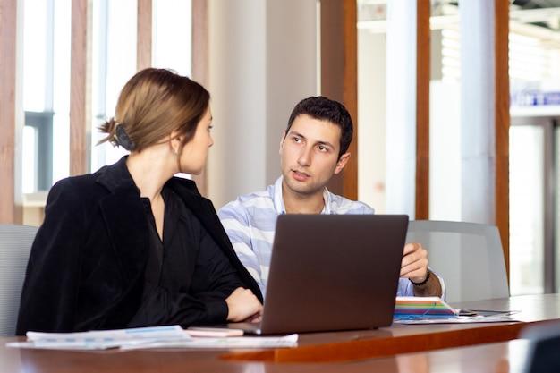Uma vista frontal jovem empresária linda camisa preta jaqueta preta, juntamente com jovem discutindo questões de trabalho dentro de seu escritório Foto gratuita