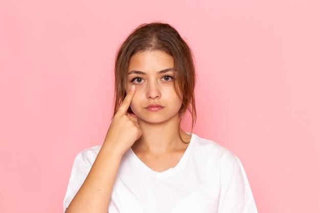 Uma vista frontal jovem fêmea bonita na camisa branca, mostrando o olho Foto gratuita