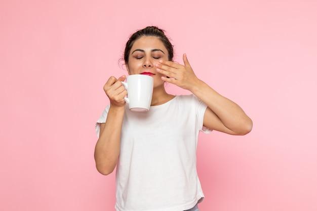 Uma vista frontal jovem fêmea em camiseta branca e calça jeans azul bebendo chá Foto gratuita
