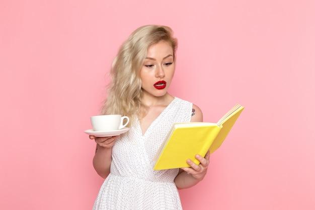Uma vista frontal linda moça de vestido branco, bebendo um chá lendo um caderno Foto gratuita