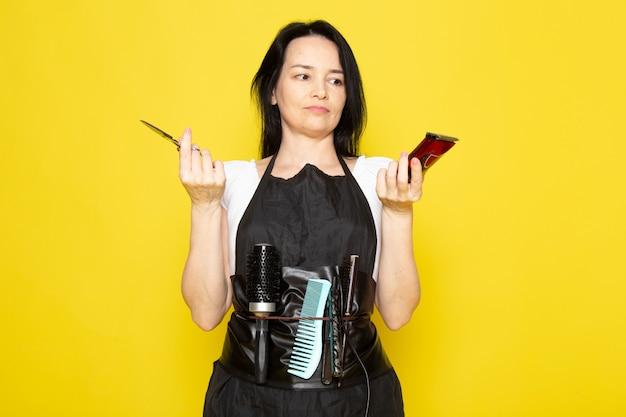 Uma vista frontal lindo cabeleireiro feminino na capa branca de camiseta preta com escovas com cabelos lavados, segurando uma tesoura e uma máquina posando no cabeleireiro estilista de fundo amarelo Foto gratuita