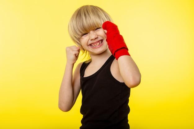 Uma vista frontal loira sorridente criança de camiseta preta e posando de boxe na parede amarela Foto gratuita