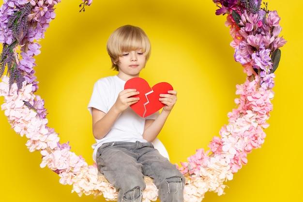 Uma vista frontal loiro menino bonitinho na camiseta branca segurando coração forma sentado sobre a flor feita ficar no chão amarelo Foto gratuita