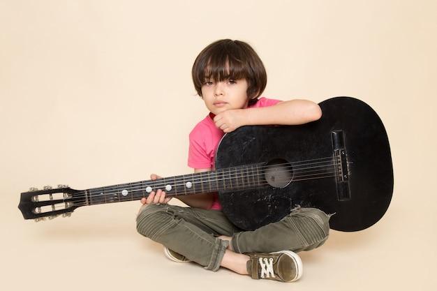 Uma vista frontal menino bonitinho deprimido em jeans cáqui t-shirt rosa tocando violão preto Foto gratuita