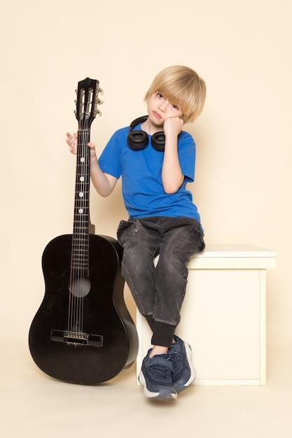 Uma vista frontal menino bonitinho na camiseta azul com fones de ouvido pretos, segurando o violão preto Foto gratuita