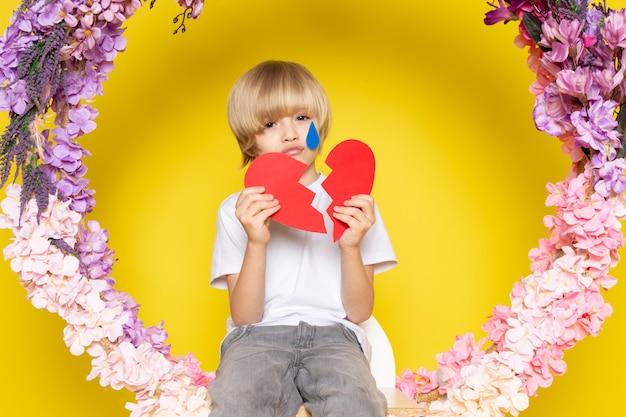 Uma vista frontal menino de cabelos loiros em camiseta branca com forma de coração, sentado na flor feita ficar no chão amarelo Foto gratuita