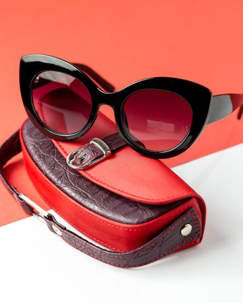 Uma vista frontal óculos escuros modernos, juntamente com bolsa de couro vermelho sobre o branco-vermelho Foto gratuita