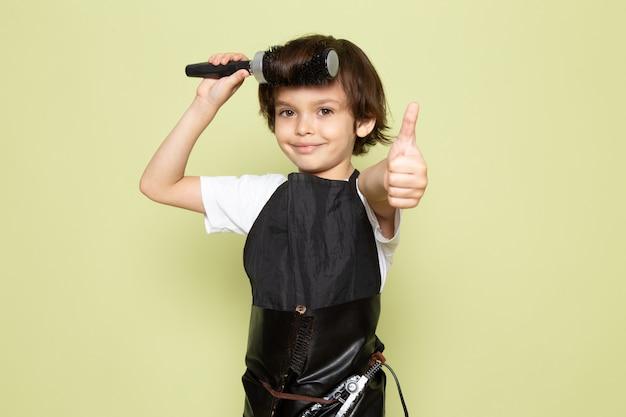 Uma vista frontal pequeno cabeleireiro criança adorável em capa preta posando Foto gratuita