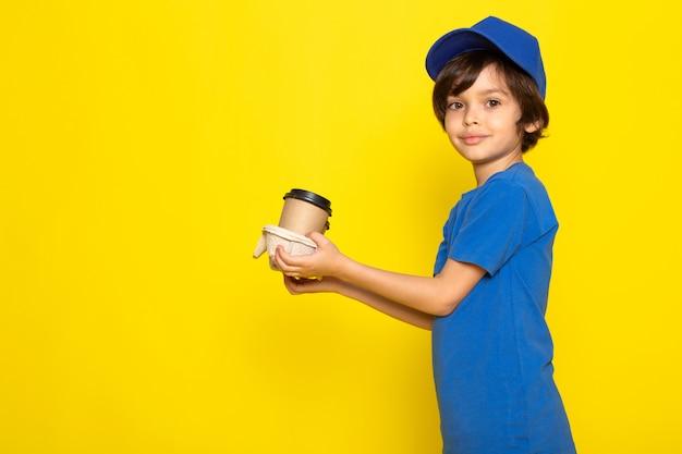Uma vista frontal pequeno correio bonito no boné azul de camiseta azul segurando copos de café Foto gratuita