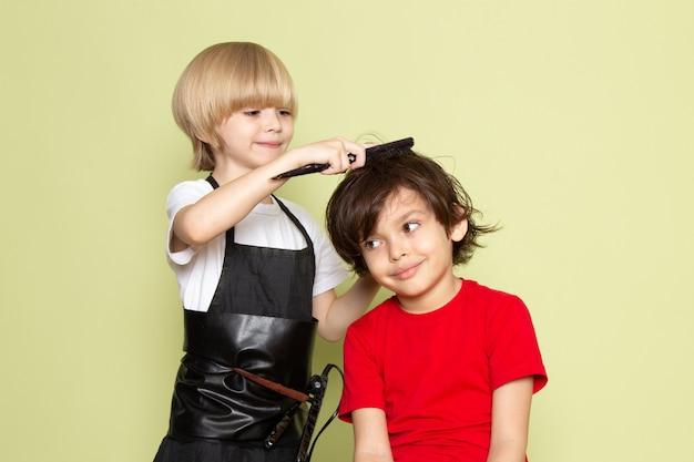 Uma vista frontal pouco cabeleireiro adorável criança adorável trabalhando Foto gratuita