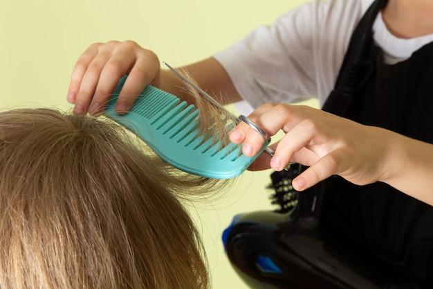 Uma vista frontal pouco cabeleireiro criança adorável trabalhando com penteado de meninos Foto gratuita