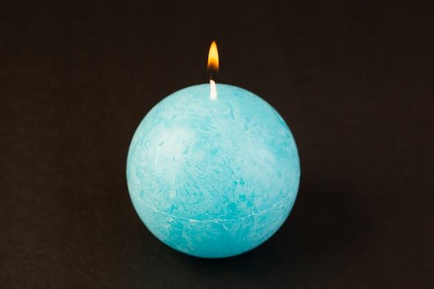 Uma vista frontal redonda em forma de vela iluminação azul colorido projetado sobre o fundo escuro brilhante decoração de fogo Foto gratuita