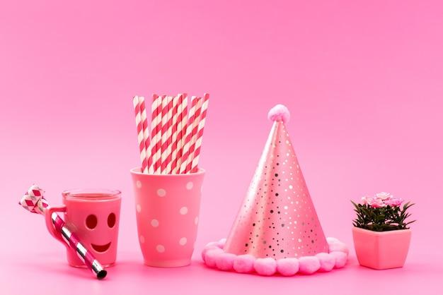 Uma vista frontal rosa, -branco, doces em forma de bastão com uma tampa de aniversário engraçada e plantinha em rosa, doce de cor fofura Foto gratuita