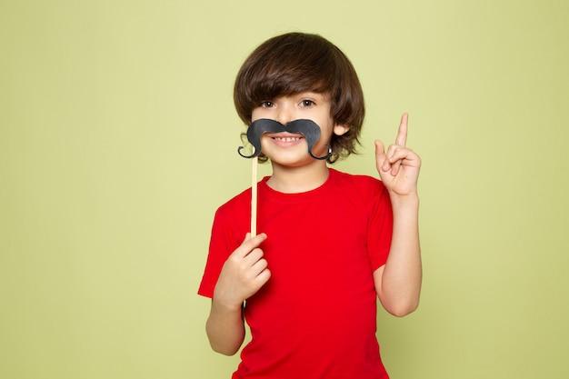 Uma vista frontal sorridente menino bonitinho na camiseta vermelha e bigode no espaço colorido de pedra Foto gratuita