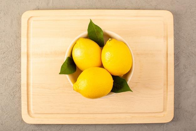 Uma vista superior amarelo limão fresco maduro maduro suculento com folhas verdes dentro da bacia branca alinhada na cor cinzenta das frutas cítricas do fundo Foto gratuita