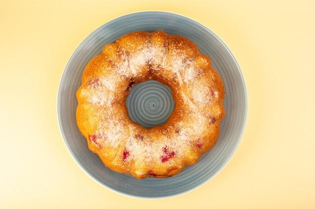 Uma vista superior assada de bolo de frutas delicioso redondo com cerejas vermelhas dentro e açúcar em pó dentro de prato redondo azul sobre amarelo Foto gratuita
