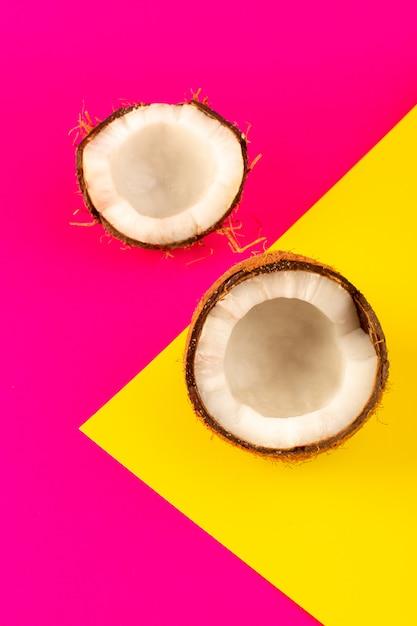 Uma vista superior, coco, fatiado, e, fresco, leitoso, maduro, isolado, ligado, a, cor-de-rosa, e, amarela Foto gratuita