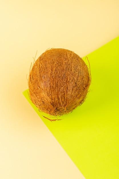 Uma vista superior cocos maduro leitoso fresco inteiro isolado no creme-pistache colorido Foto gratuita