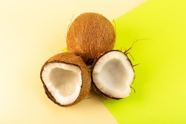 Uma vista superior cocos maduros frescos leitosos inteiros e fatiados isolados no pistache creme colorido Foto gratuita