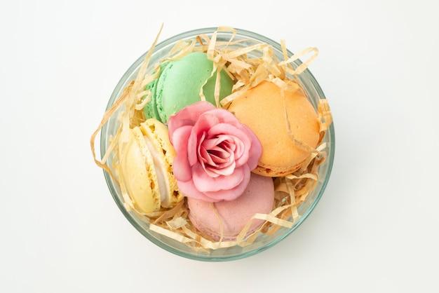Uma vista superior colorida de macarons franceses redondos formados deliciosos dentro de um vidro redondo em branco, cor de biscoito de bolo Foto gratuita
