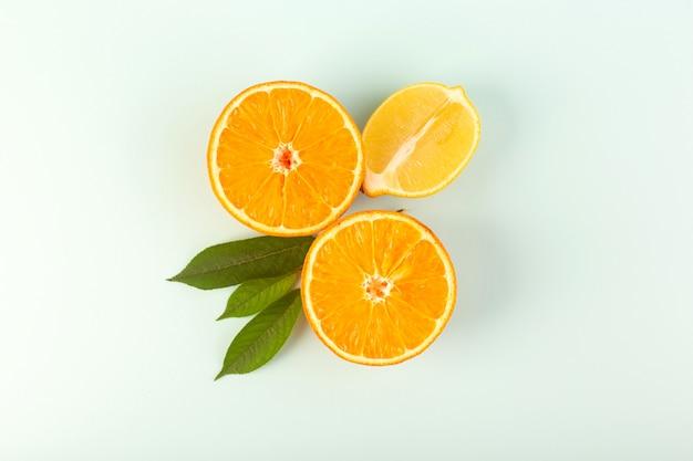 Uma vista superior cortada laranja madura madura suculenta fresca isolada metade cortada com folhas verdes sobre o fundo branco cor de frutas cítrico Foto gratuita