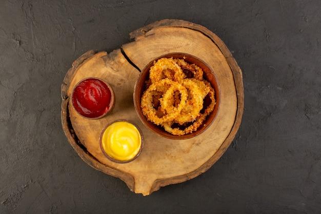 Uma vista superior de anéis de frango frito dentro de um prato marrom com ketchup e mostarda Foto gratuita