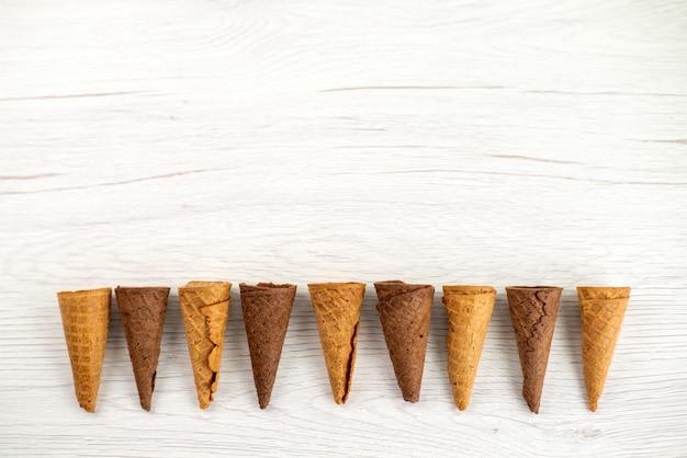 Uma vista superior de chifres de sorvete deliciosos em branco, doce de sorvete de sobremesa Foto gratuita