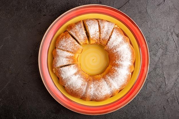 Uma vista superior doce redondo bolo com açúcar em pó fatiado doce delicioso bolo isolado dentro da placa e fundo cinza biscoito de açúcar Foto gratuita
