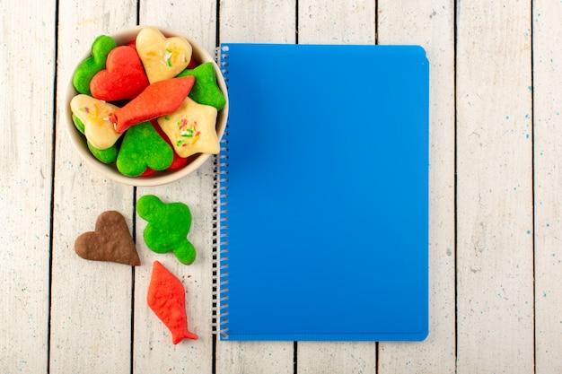 Uma vista superior multicoloridos deliciosos biscoitos diferentes formados placa interna com caderno azul na superfície cinza Foto gratuita